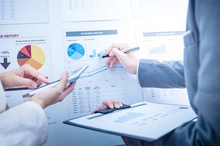 GERENTE: La gente de negocios en discusiones sobre los cuadros y gráficos que muestran los resultados de su trabajo en equipo éxito