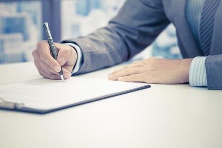 ビジネスの男性が契約に署名します。