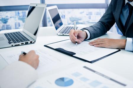 Geschäftsleute, die in die Charts und Diagramme, die die Ergebnisse ihrer erfolgreichen Zusammenarbeit
