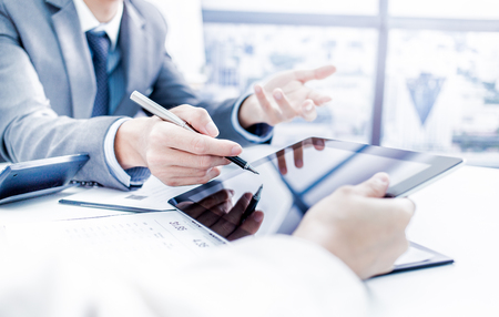ejecutiva en oficina: La gente de negocios en discusiones sobre los cuadros y gráficos que muestran los resultados de su trabajo en equipo éxito