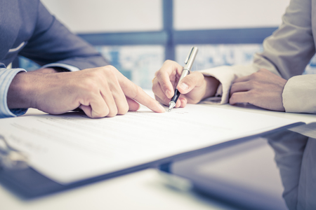 business  deal: Female hand signing contract. Stock Photo