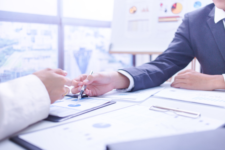 financial concept: Two businessmen looking at report and having a discussion in office. Stock Photo