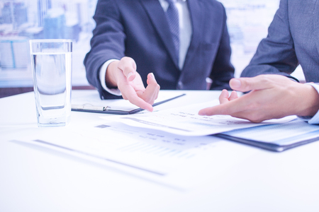 account executives: Two businessmen looking at report and having a discussion in office. Stock Photo
