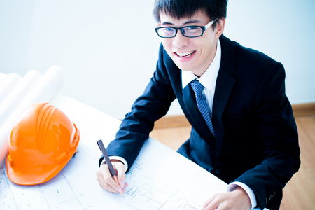 draftsman: Closeup cropped image of a young male architect working on blueprints spread out on a table Stock Photo