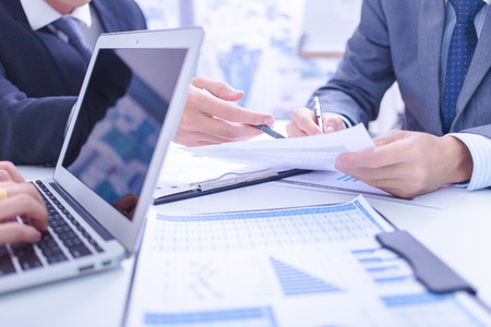 chinese businessman: Two businessmen looking at report and having a discussion in office. Stock Photo