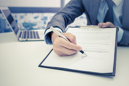 contracts: Business man signing a contract Stock Photo