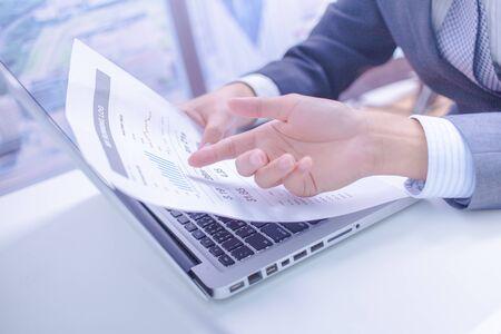 informe: Dos hombres de negocios que buscan en el informe y que tienen una discusión en el cargo.