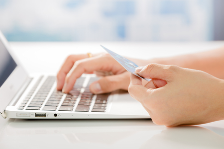 compras: Manos De La Mujer que sostiene la tarjeta de crédito y computadora portátil. Las compras en línea
