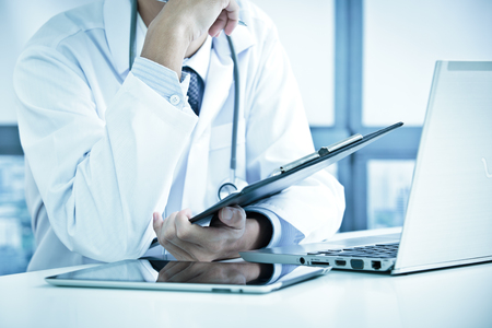 inputting: Close-up of a medical worker with laptop Stock Photo