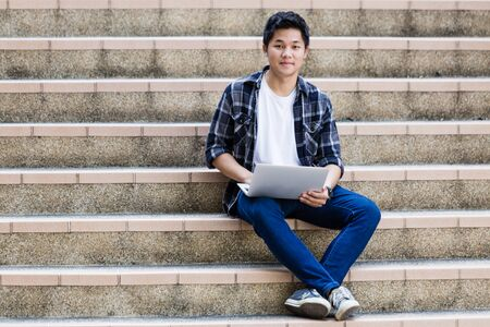 Young man sitting on the stairs using laptop