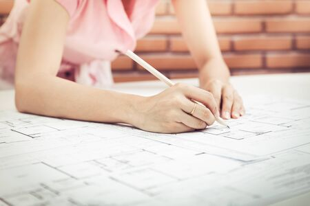 asian architect: Female architect working at home.She looking at blueprint.