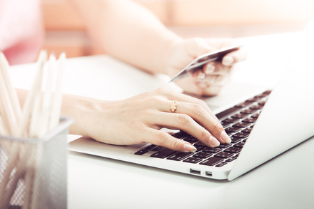 woman typing: Woman Hands holding credit card and using laptop. Online shopping