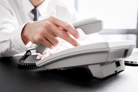 loseup of dialing a telephone number on a black landline telephone Foto de archivo