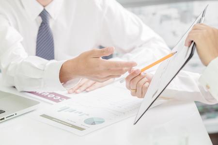 bonhomme blanc: Les gens d'affaires discutant des tableaux et des graphiques montrant les résultats de leur travail d'équipe réussie