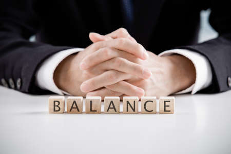 inform information: Close up Hand of a Businessman Arranging Small Wooden Blocks with balance words on blocks