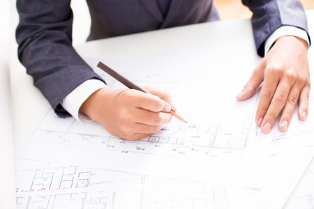 cropped out: Closeup cropped image of a young male architect working on blueprints spread out on a table Stock Photo
