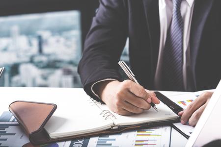 Unternehmensberater analysieren Finanzzahlen bezeichnet die Fortschritte bei der Arbeit des Unternehmens Standard-Bild
