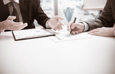 personas hablando: Dos hombres de negocios que buscan en el informe y que tienen una discusión en el cargo.