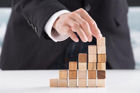 조직: 빈 나무 큐브와 피라미드를 만드는 사업가의 근접 촬영