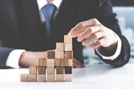 pyramid: Closeup of businessman making a pyramid with empty wooden cubes