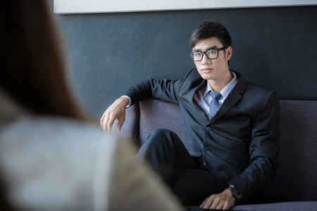 telephone interview: Young businessman sitting on sofa at office listening to talking businesswoman. Stock Photo