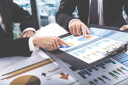 그들의 성공적인 팀웍의 결과를 보여주는 차트 및 그래프를 논의하는 사업 사람들