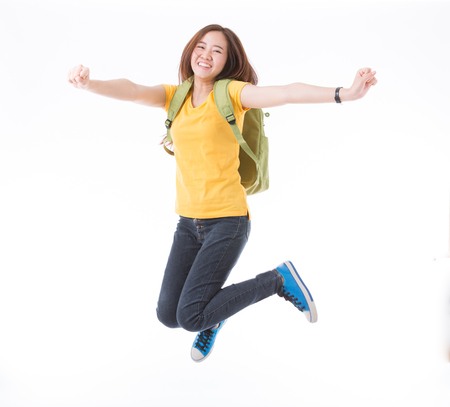 Jumping female college / university student isolated on white background. Young woman Asian Caucasian students. Standard-Bild