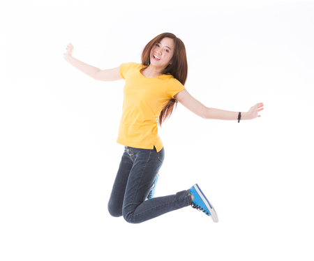 Jumping female college / university student isolated on white background. Young woman Asian Caucasian students. Archivio Fotografico