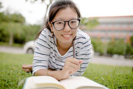 persona leyendo: Un estudiante universitario de sexo femenino que lee un libro mientras está acostado en el parque Foto de archivo