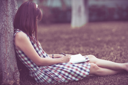 girl studying: Close-up of a young girl writing into her diary, in the park