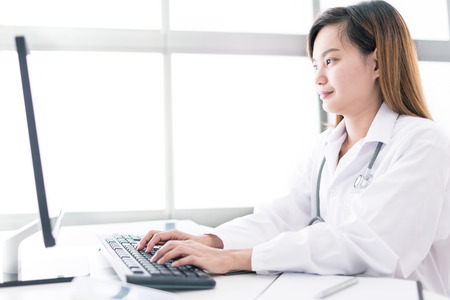 health professional: Portrait of a smiling physician working in her office. Asia