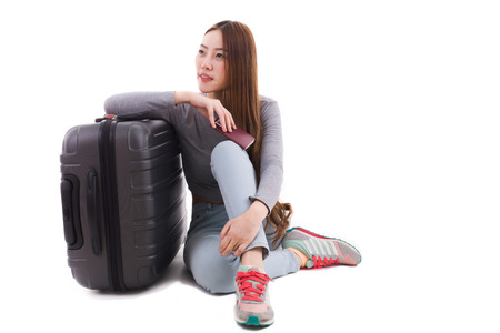 Woman sitting near a suitcase on a white background.