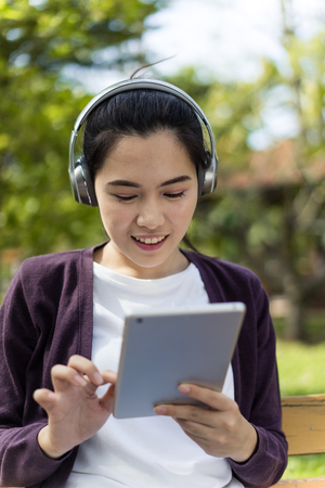 Young woman using tablet in park Stock Photo