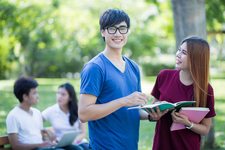 higher education: Group of students sharing with the ideas on the campus lawn