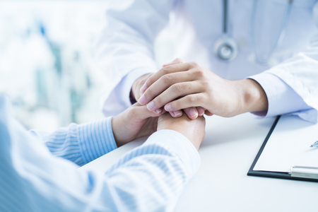 male doctor comforting patient at consulting room