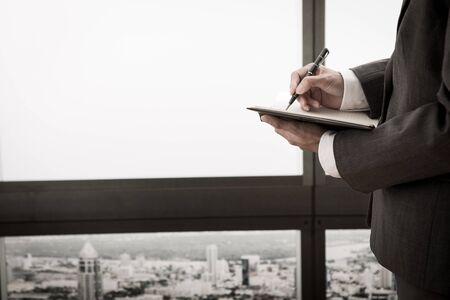 datebook: businessman writes in datebook