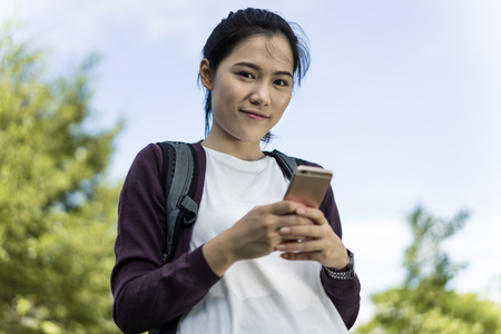 sit down: Side view of a college girl text messaging  in the park