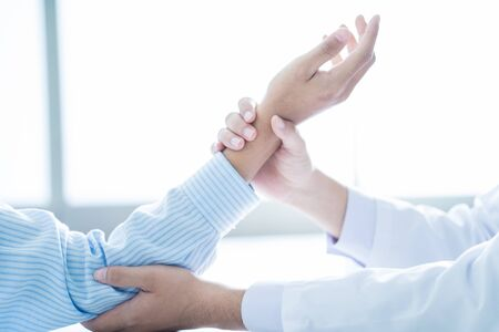 orthopedist: Orthopedist examining injured arm of male patient Stock Photo