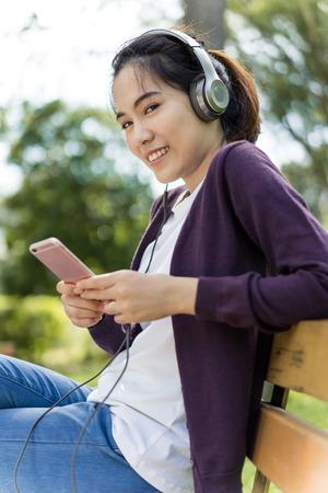 pretty women in the park listening music