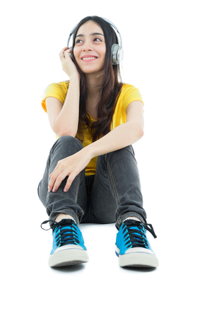Young motion woman with headphones listening music on white background.