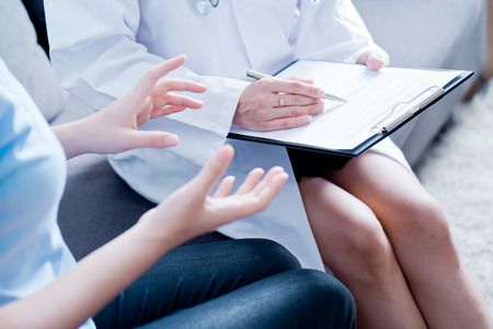 Woman doctor talking to her male patient at office Stock Photo
