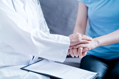 oncologist: Hand of doctor reassuring her female patient Stock Photo