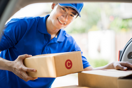 Delivery concept - postman in blue uniform holding package