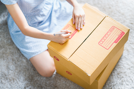 Woman signs papers among parcels. Delivery concept Zdjęcie Seryjne