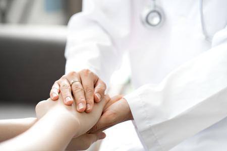 Hand van arts geruststellend haar vrouwelijke patiënt Stockfoto - 80123142