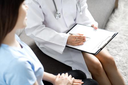 Médico de la mujer hablando con su paciente de sexo masculino en la oficina