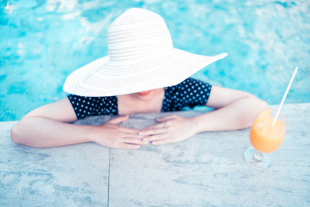 outerwear: Young woman with cocktail in swimming pool