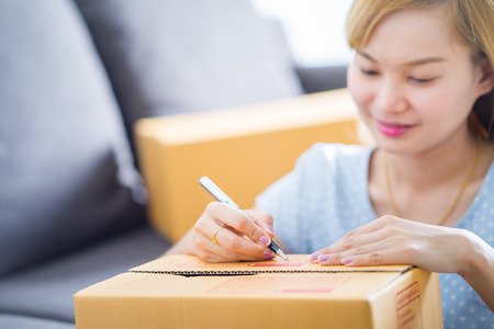 autograph: Woman signs papers among parcels. Delivery concept Stock Photo