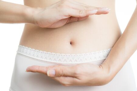 Woman torso showing her navel. white background Stock Photo