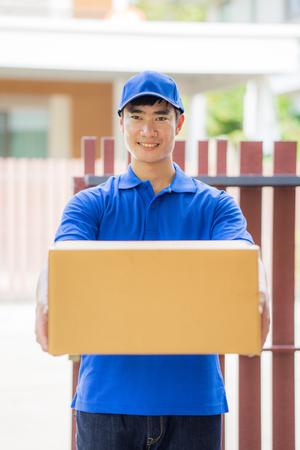 Concept de livraison - postier dans l & # 39 ; uniforme bleu tenant paquet Banque d'images - 80759463